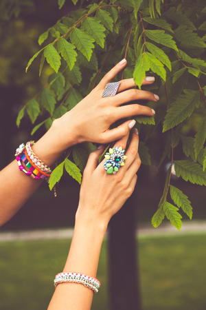 touch: closeup of female hands with large rings and bracelets touch  leaves on tree
