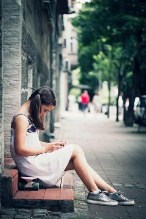 street shot: teen girl in white dress sit on skate use smartphone street shot summer day Stock Photo