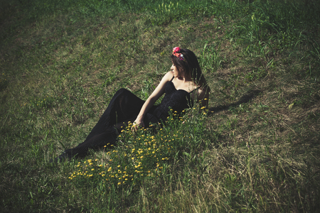 full shot: young woman in black dress and wreath of flowers lie on summer grass full body shot Stock Photo