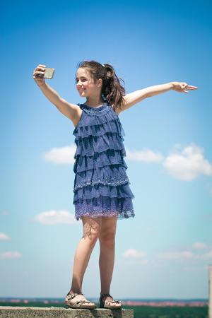 beautiful teen: cute girl in summer dress make selfie on roof top summer day full body shot