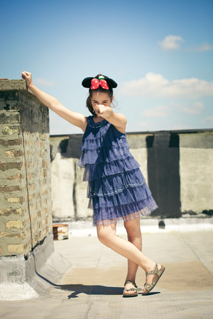 minnie mouse: teen girl point with finger with minnie mouse ears outdoor at terrace on roof summer day full body shot