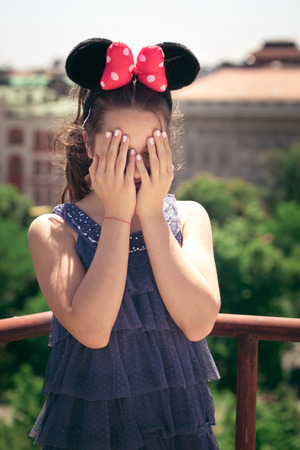 minnie mouse: teen girl portrait with minnie mouse ears cover face with hands outdoor at building  terrace summer day Stock Photo