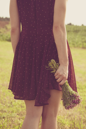 lower body: young woman in red dress and bouquet of wild flowers back shot lower body