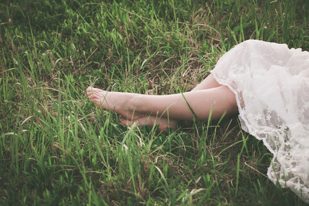 lacy: woman in white lacy dress barefoot legs on grass close Stock Photo