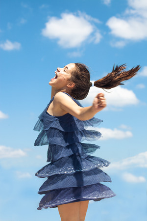 summer dress: happy smiling girl in blue dress spin around summer day against blue sky