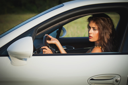 miror: attractive young woman drive car summer day