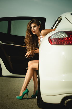 get out: attractive woman in high heel shoes get out the car summer day on the road Stock Photo