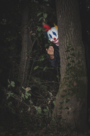 inviting: scary clown behind tree inviting with hand gesture night scene