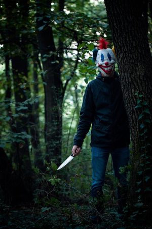 scary clown: scary clown with big knife in wood