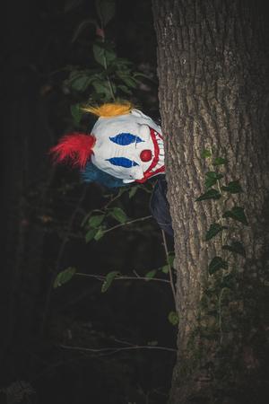 clown effrayant derrière l'arbre dans la scène de nuit de parc