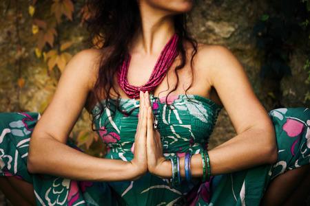 La mujer la práctica de yoga al aire libre cerca de las manos en gesto de Namaste Foto de archivo - 63850314