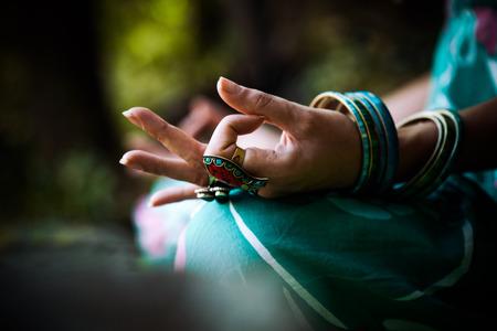 simbolo de la mujer: Primer plano de la mano de la mujer con los anillos y las pulseras de la práctica de yoga al aire libre disparo Foto de archivo