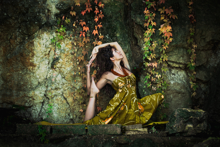 vitality: young woman practice yoga outdoor shot in front of rock with autumn leaves
