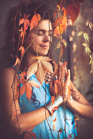 outdoor shot: woman in yoga meditation outdoor shot behind leaves autumn day Stock Photo