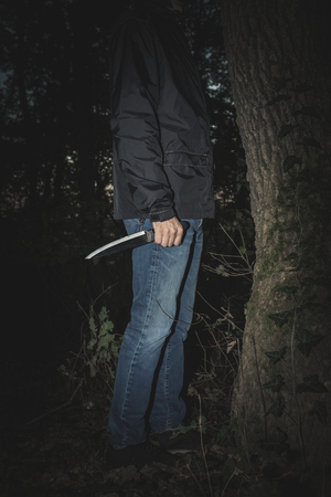 man hand hold knife in the wood lower part of body