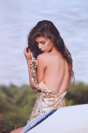 lean back: sensual young woman in golden dress bare back lean on car outdoor shot summer day
