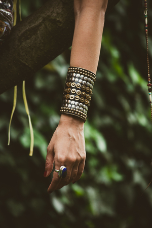 outdoor shot: ring and massive bracelet on woman hand outdoor shot closeup