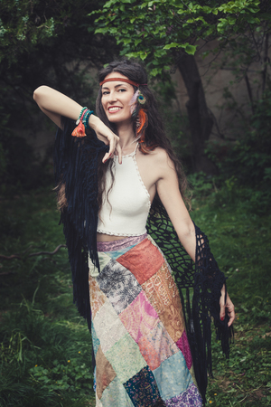 smiling young woman in boho style clothes outdoor shot