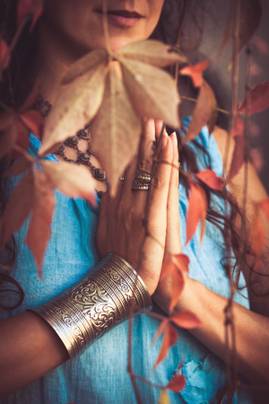 outdoor shot: close up of woman hands in namaste gesture outdoor shot behind leaves