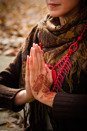 color tribal tattoo: closeup of woman hands in yoga position  with henna drowing outdoor shot