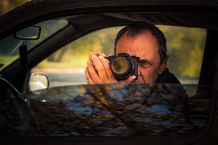 secretly: undercover man detective hidden in car secretly take photo