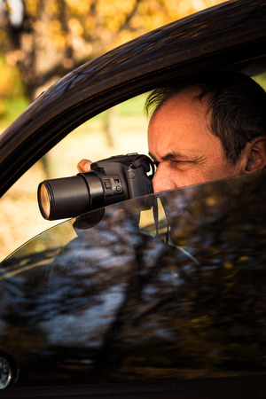 undercover: undercover man detective hidden in car secretly take photo