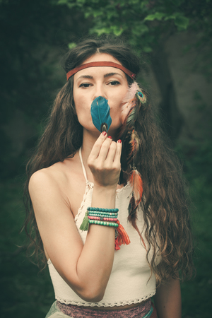 beautiful bohemian fashion style young woman with feather portrait outdoor summer day