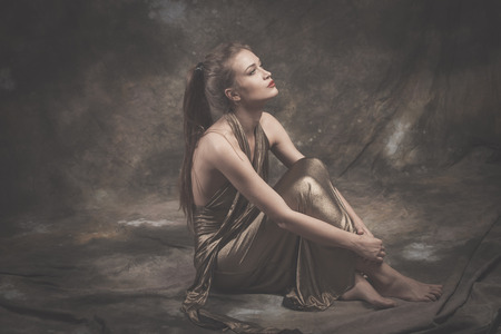 sit on studio: barefoot elegant young woman in golden dress sit full body shot studio