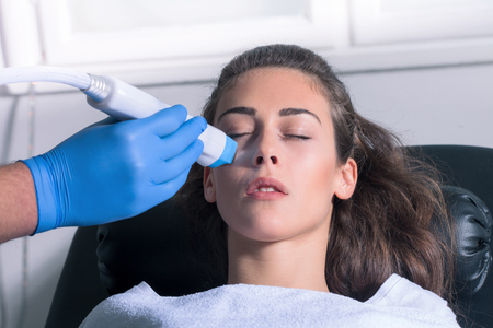 fractional: woman face fractional treatment at medical spa center