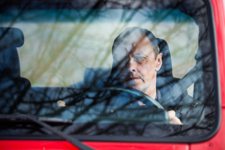 sky reflection: man in his car behind wheel front view through the glass reflection of trees and sky in glass