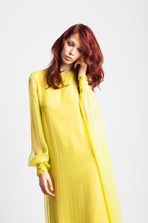 sho: beautiful red-haired girl in long elegant yellow dress  studio sho Stock Photo