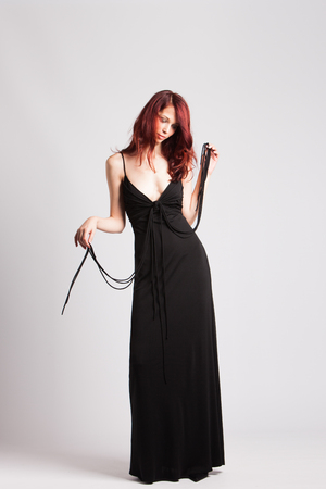 feminine beauty: fashion model red-haired girl in long black evening dress studio shot