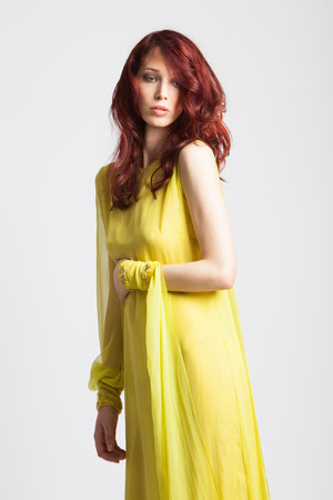 beautiful red-haired girl in long elegant yellow dress  studio shot