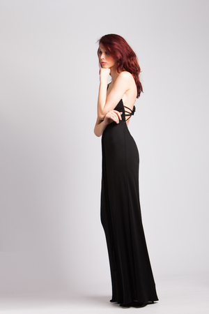 beautiful red-haired girl in long black evening dress studio shot photo