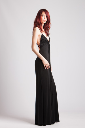young attractive red-haired girl in long black evening dress studio shot photo