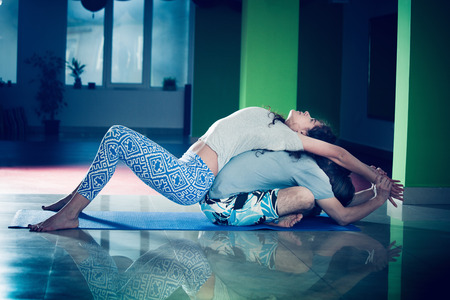 young man and woman doing yoga  indoor healthy lifestyle concept