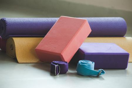 closeup of yoga blocks belts and mat props indoor Stock Photo