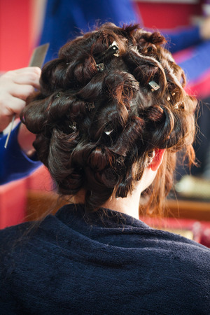 curling: young woman at hairdresser curling hair closeup