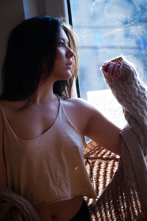 maturation: beautiful pensive young woman by the window portrait  Stock Photo