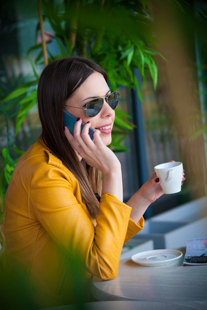 urban girl sit in cafe outdoor with coffee talking on smartphone spring day city life concept