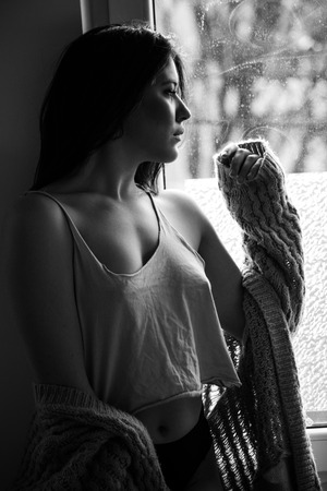maturation: beautiful pensive young woman by the window portrait in bw Stock Photo