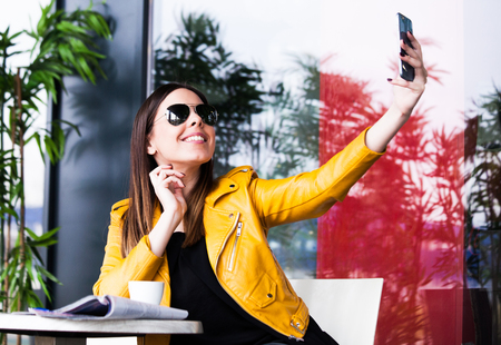 smiling  girl in cafe outdoor  taking selfie on smartphone spring day city life concept