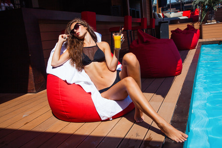 girl in bikini take sunbath by pool holding glass of cold juice  hot summer day photo