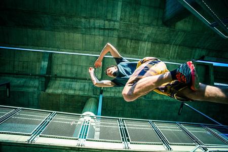 joven la práctica del parkour salto en las escaleras en la captura de la ciudad deporte extremo concepto de desde abajo Foto de archivo