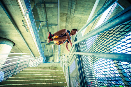 extreme sports: young man practice parkour jump on stairs with metal fence  in the city extreme sport concept