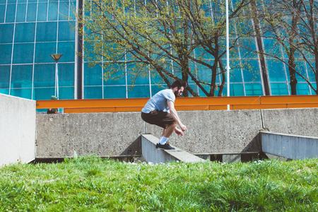 joven haciendo parkour en el espacio urbano en la ciudad suuny primavera día de verano Foto de archivo