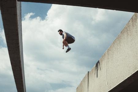 joven haciendo parkour saltar en el espacio urbano en la ciudad soleada primavera día de verano