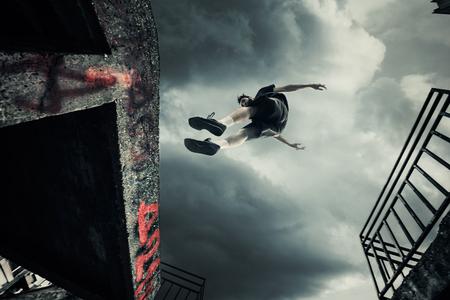 都市の下からショットでパルクール ジャンプをやって若い男 写真素材