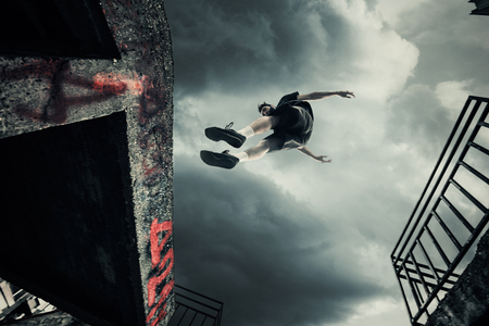 young man doing parkour jump in the city shot  from below
