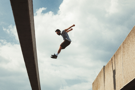 acrobatics: young man doing parkour jump in urban space in the city  sunny spring summer day